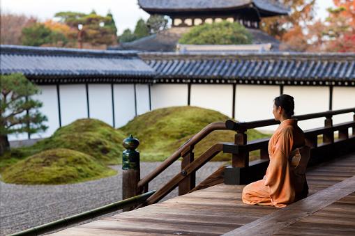 A woman wearing a a kimono walking through a temple.