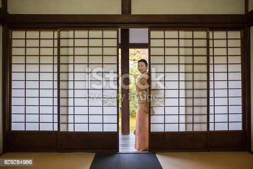 A woman in a kimono about to pass through some traditional sliding doors at a temple in Japan