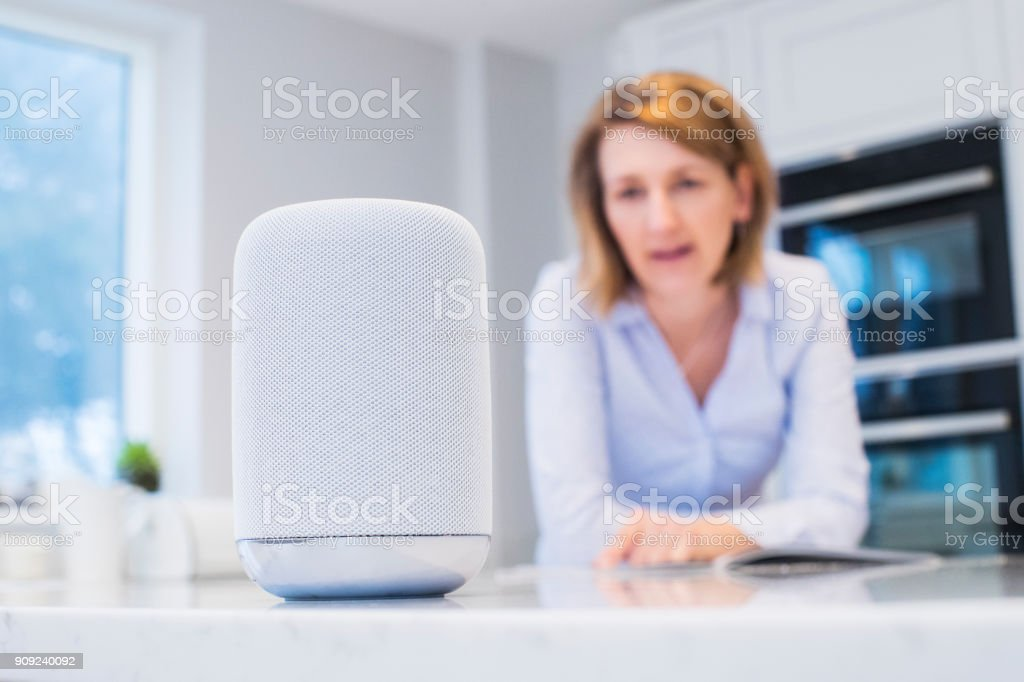 Woman In Kitchen Asking Digital Assistant Question stock photo