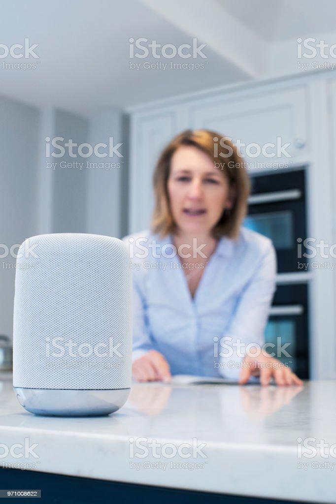 Mulher na cozinha fazendo pergunta assistente Digital - foto de acervo