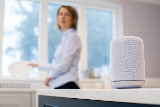 Mulher na cozinha perguntando assistente Digital enquanto lavar - foto de acervo