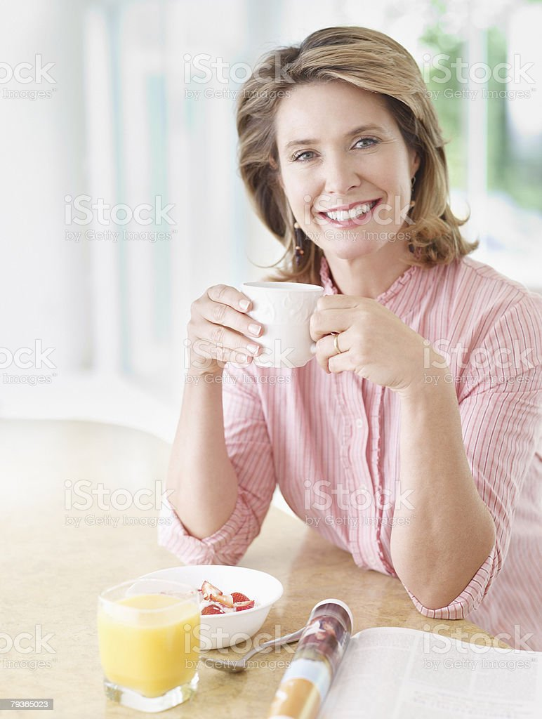 Woman in kitchen eating breakfast stock photo