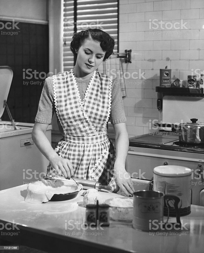 Woman in kitchen making pie (B&W) stock photo