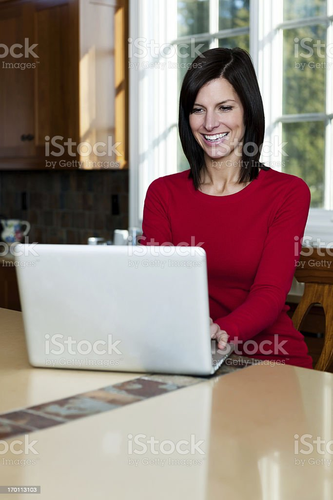 Woman in kitchen on notebook computer royalty-free stock photo
