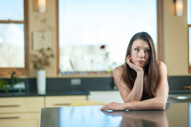 Woman in Kitchen Dark haired woman in kitchen leaning on counter. rolling eyes stock pictures, royalty-free photos & images