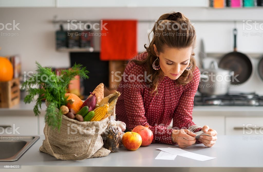 Woman in kitchen reading shopping list stock photo
