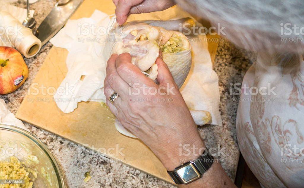 Woman in kitchen sewing a stuffed chicken to be roasted foto royalty-free