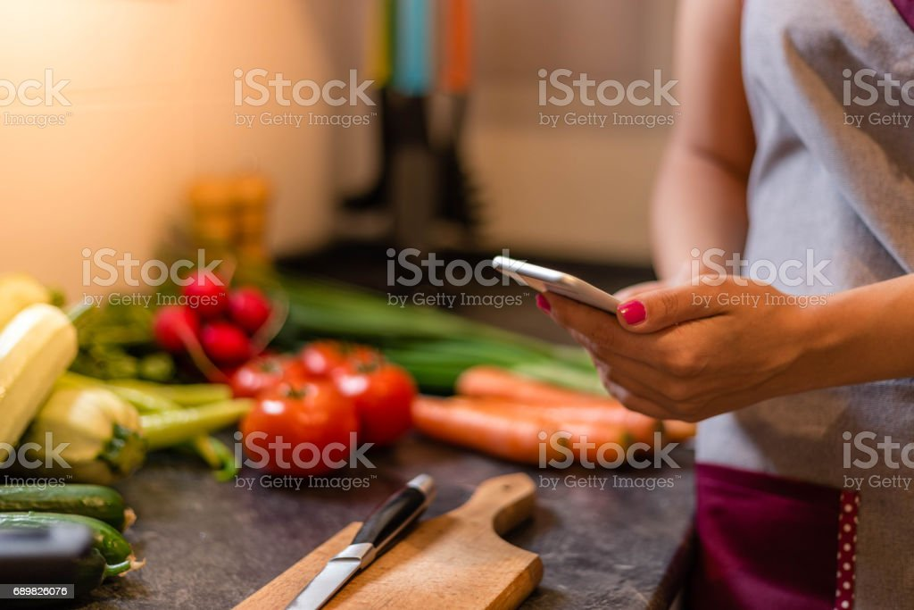 Woman in kitchen using smart phone stock photo