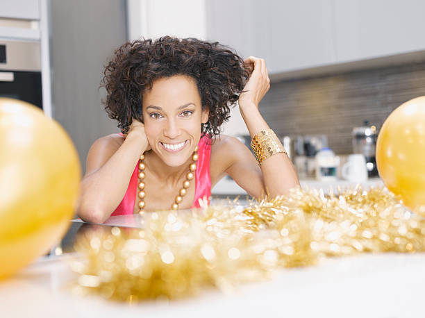 frau in der küche mit weihnachts-party dekoration - jamaikanische party stock-fotos und bilder