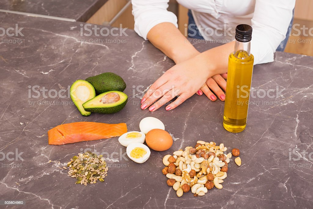 Woman in kitchen with different raw foods stock photo