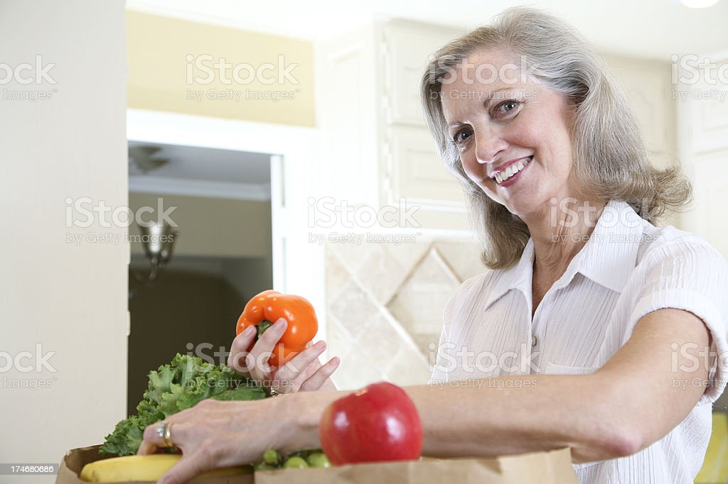 Woman in Kitchen with Fruits and Vegetables royalty-free stock photo