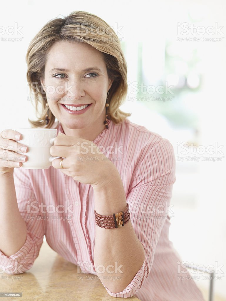 Woman in kitchen with mug royalty-free stock photo