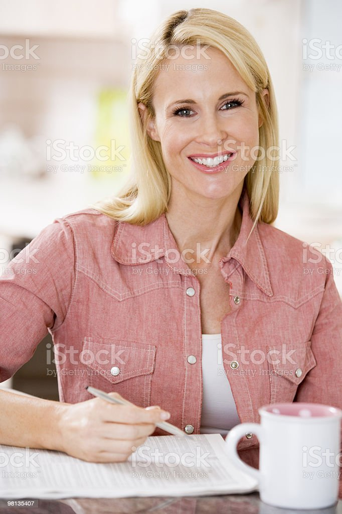 Woman in kitchen with newspaper and coffee royalty-free stock photo