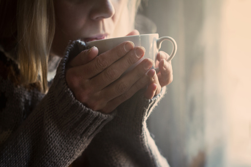 Woman in knitted sweater hands holding a cup warm coffee