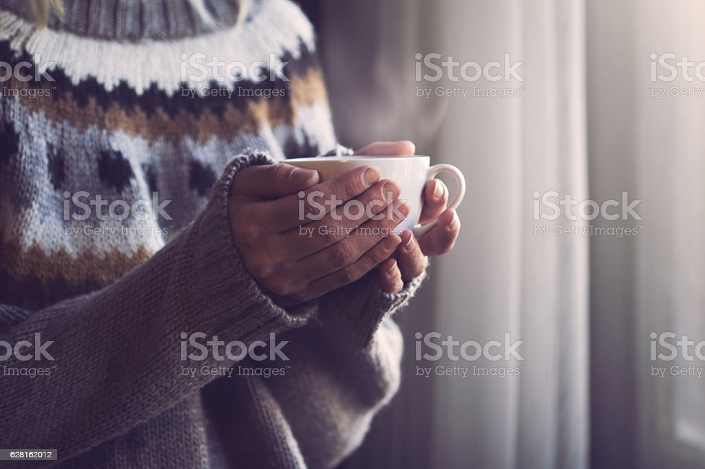 Woman in knitted sweater hands holding cup of warm coffee - foto de stock