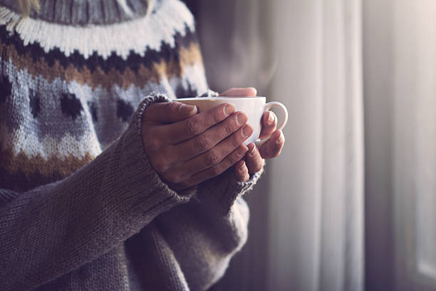 woman in knitted sweater hands holding cup of warm coffee - warm house stock photos and pictures