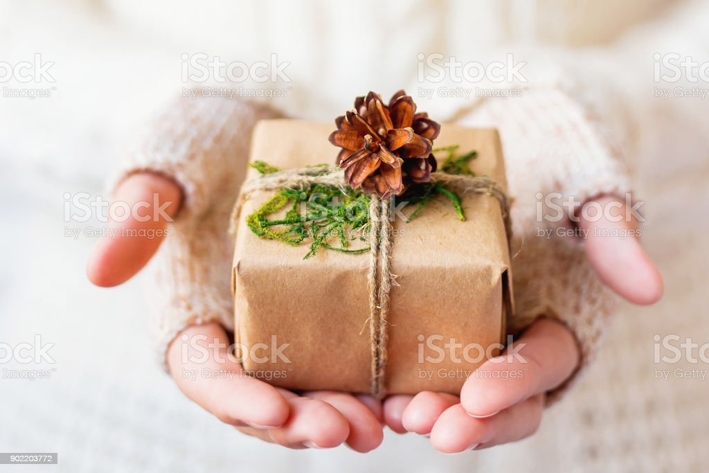 Woman in knitted sweater holding a present. Gift is packed in craft paper with pine cones and tied with rough rope. Example of DIY way to wrap a present. Place for your text. stock photo