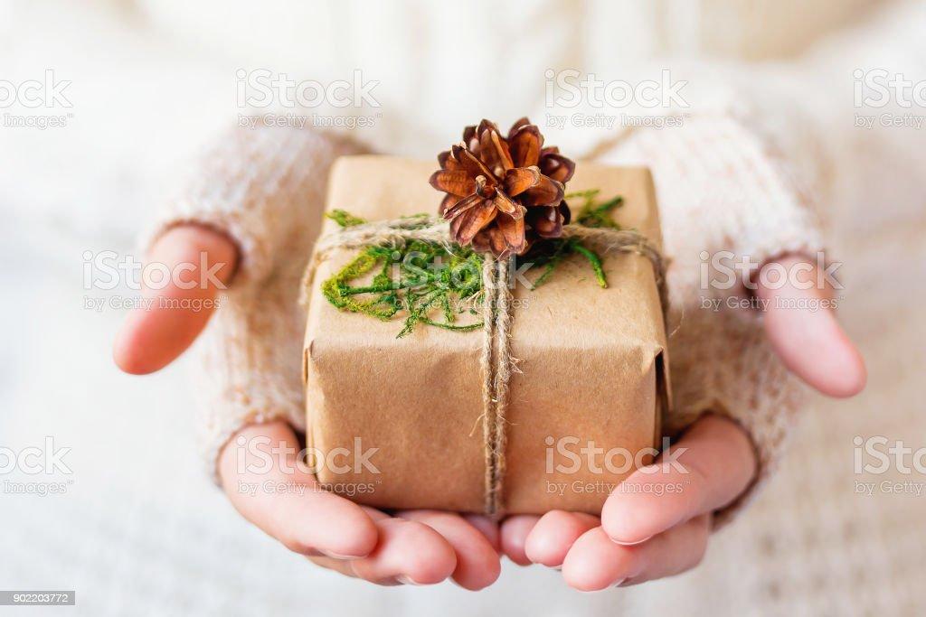 Frau in Strickpullover hält ein Geschenk. Geschenk verpackt in Kraftpapier mit Tannenzapfen und mit einem rauhen Seil gefesselt. Beispiel für DIY Weg, um ein Geschenk zu verpacken. Platz für Ihren Text. – Foto