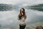 Young Caucasian woman in knitted sweater  laughing near the  fjord in Norway