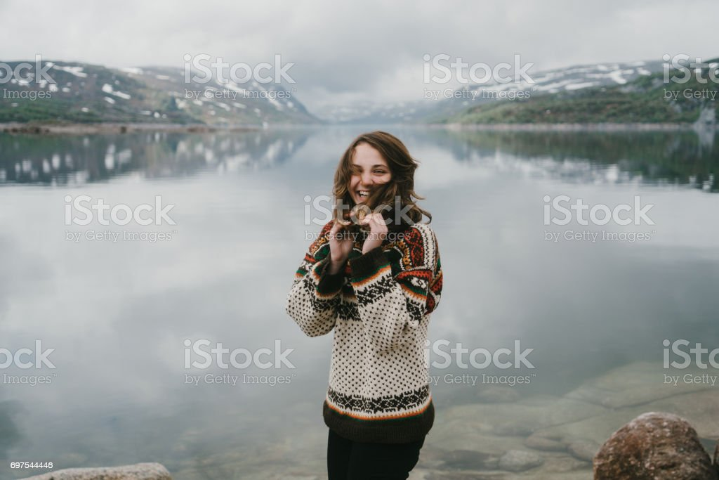 Woman in knitted sweater laughing near the  fjord in Norway stock photo