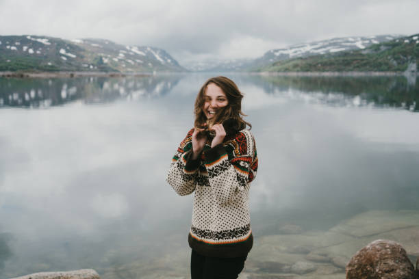woman in knitted sweater laughing near the  fjord in norway - nordic countries stock pictures, royalty-free photos & images