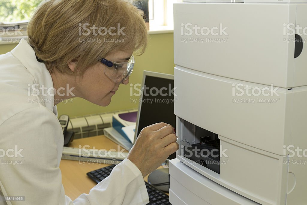 woman in laboratory add samples to hplc stock photo