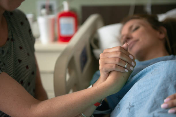 a woman in labour grips the hand of a support person stock photo - showus стоковые фото и изображения
