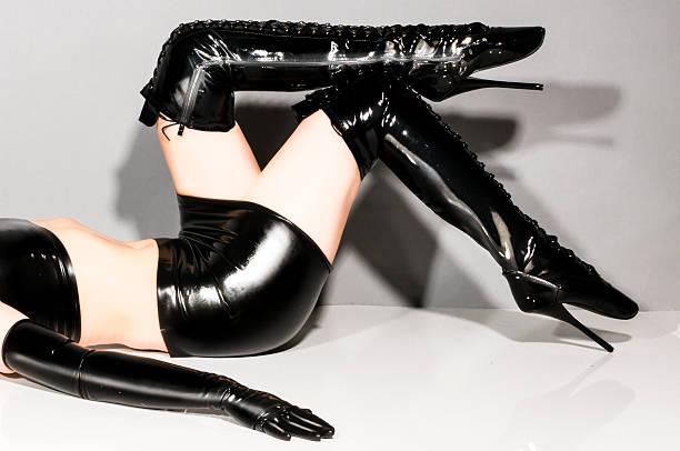 frau in latex-kleidung mit ihrem stiefel - damen rock kostüme stock-fotos und bilder