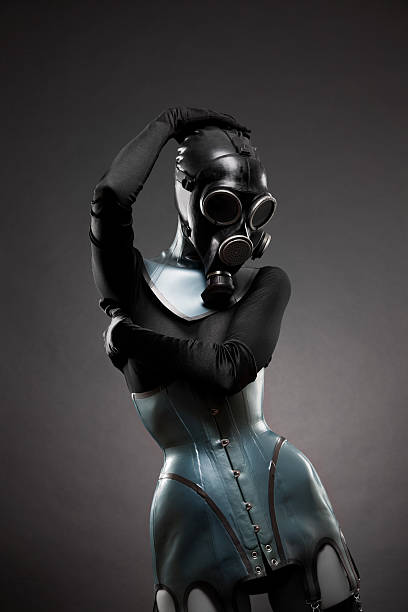 Woman in latex corset and gas mask stock photo