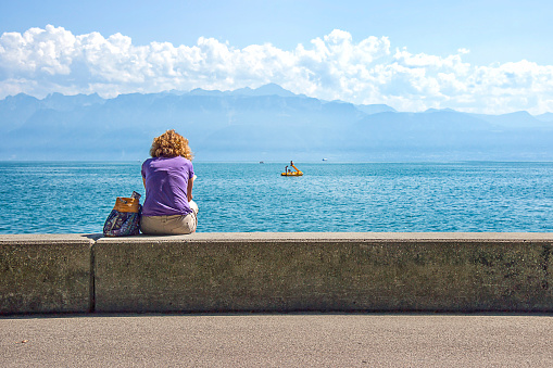 Woman in Lausanne quay of Geneva Lake in summer