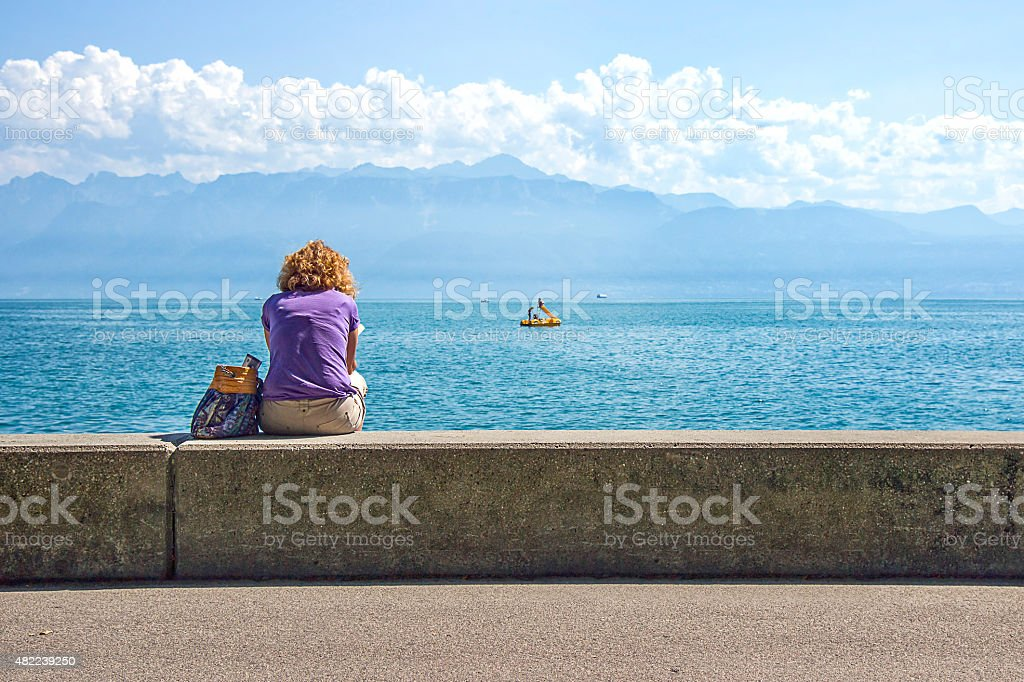 Woman in Lausanne quay of Geneva Lake in summer stock photo