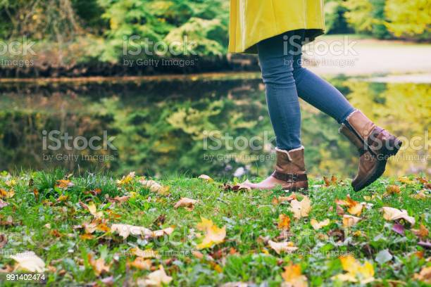 Photo of woman in leather boots is walking in an autumn park next to a lake
