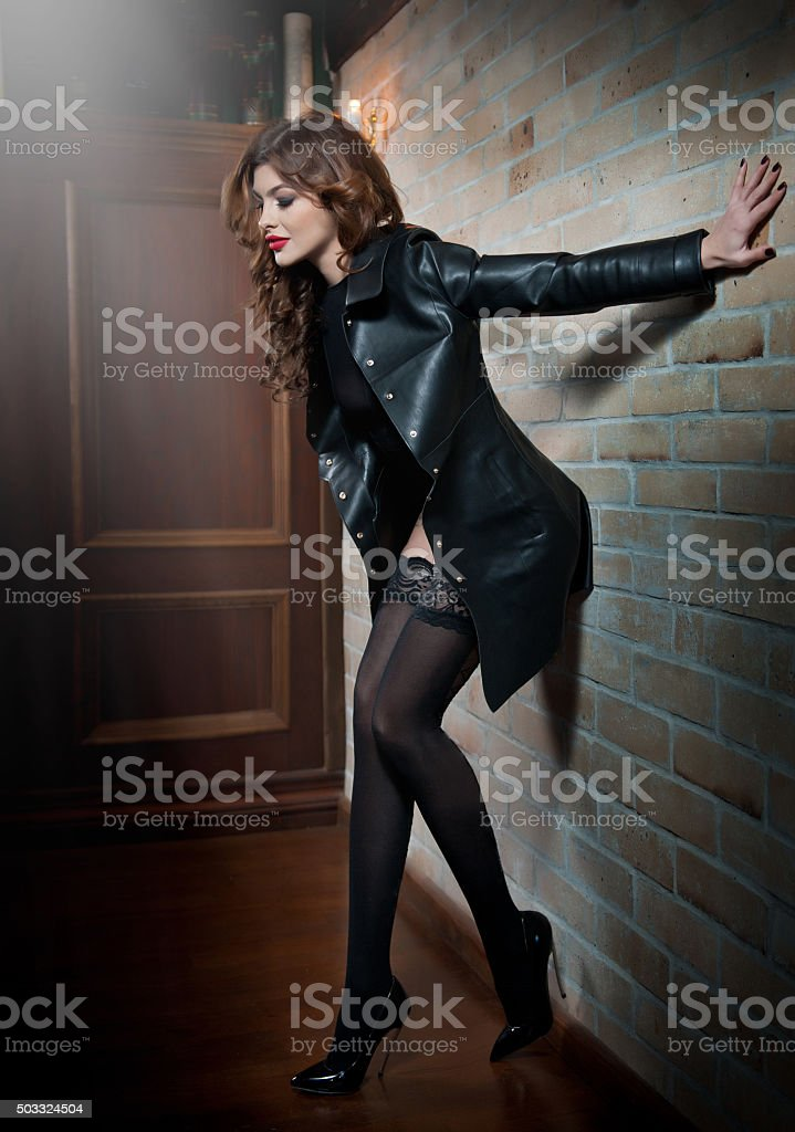 woman in leather coat over black stockings stock photo
