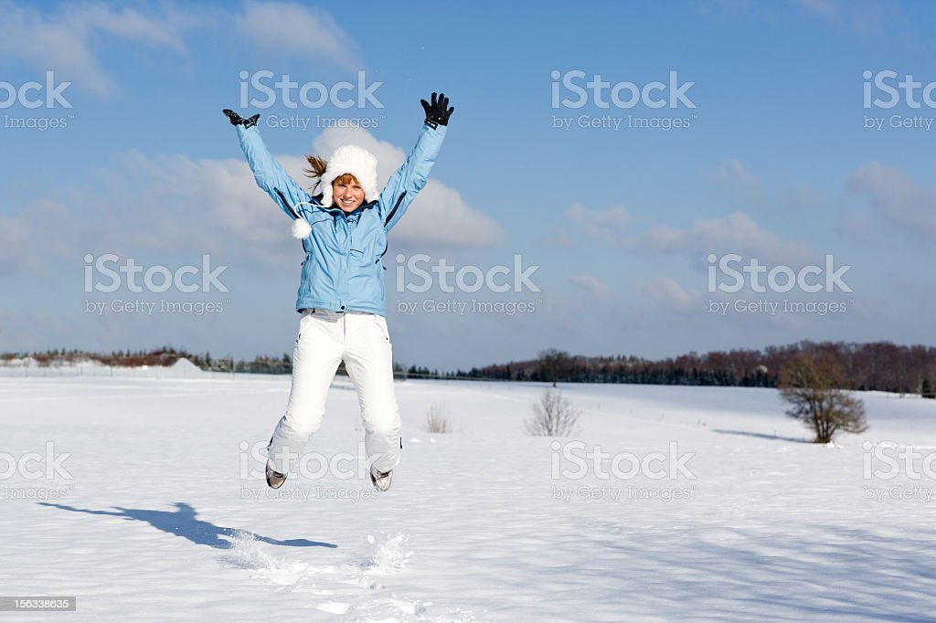 Woman in light blue jacket jumping and throwing snowball royalty-free stock photo