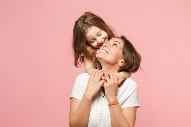 Woman in light clothes have fun with cute child baby girl. Mother, little kid daughter isolated on pastel pink wall background, studio portrait. Mother's Day, love family, parenthood childhood concept stock photo