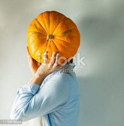 istock A woman in light clothes holds a large ripe pumpkin instead of a head. Food concept joke. 1170818304