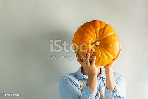 istock A woman in light clothes holds a large ripe pumpkin instead of a head. Food concept joke. 1175695686