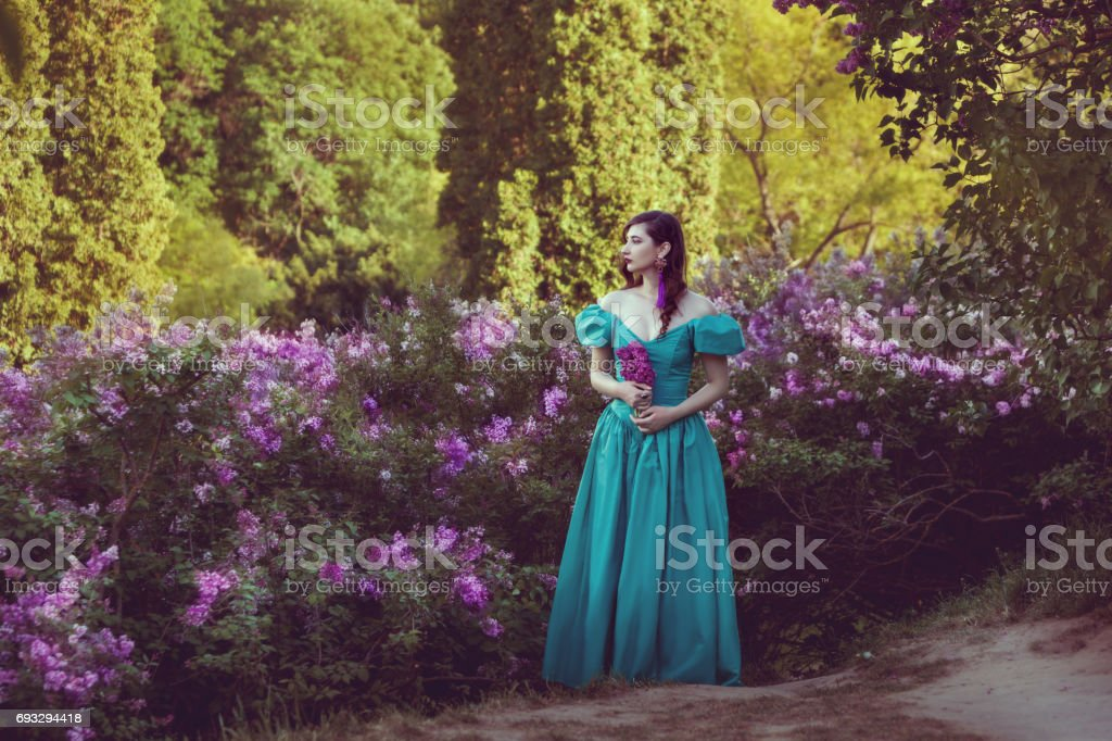 Woman in lilac bushes of lilac. stock photo