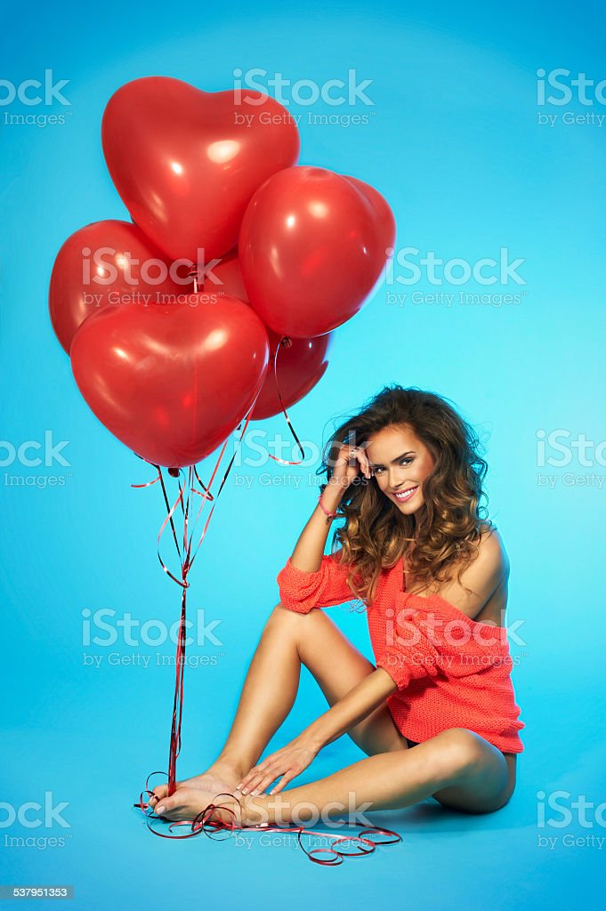 Woman in lingerie holding red heart shaped balloons Young happy girl in lingerie with red, heart shaped balloons, sitting on the floor and smiling adorable over isolated blue background, partial nudity 2015 Stock Photo