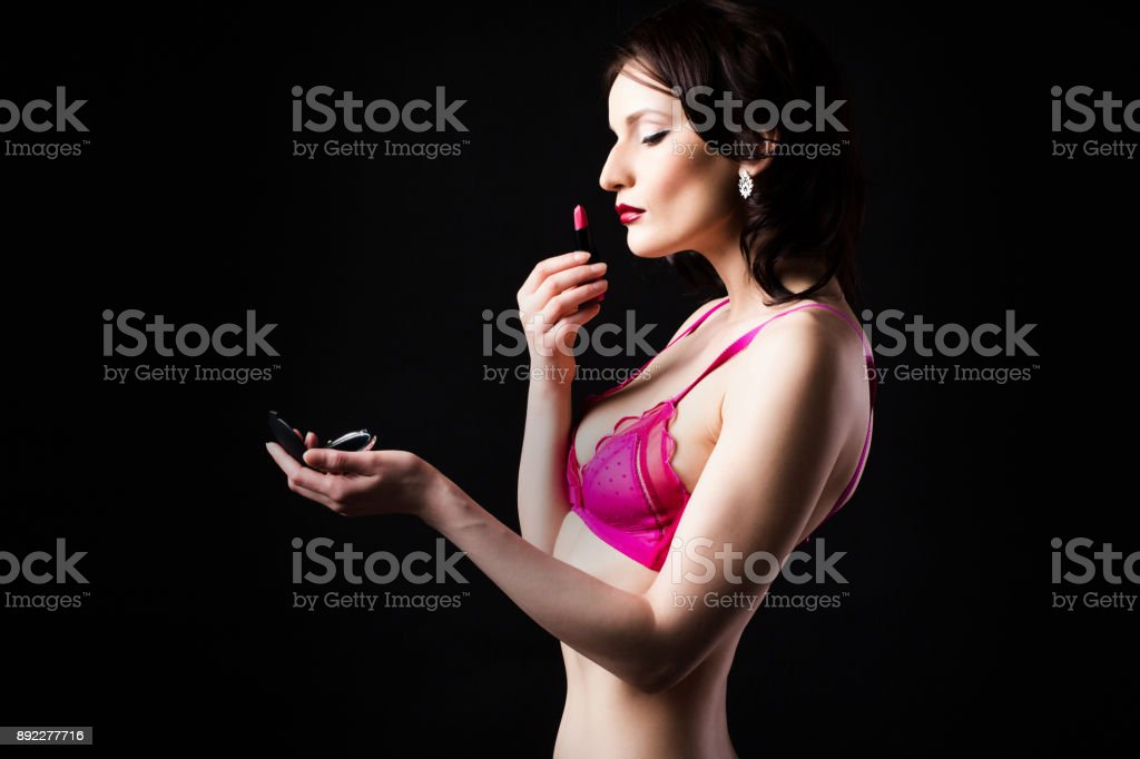 296f4c2b805 Woman in lingerie holds a red lipstick on a dark background. royalty-free  stock