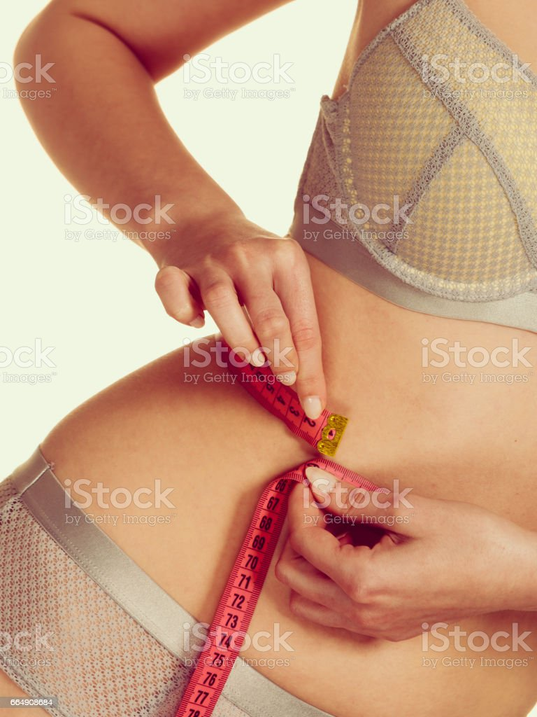 Woman in lingerie measuring her waist with measure tape. foto stock royalty-free