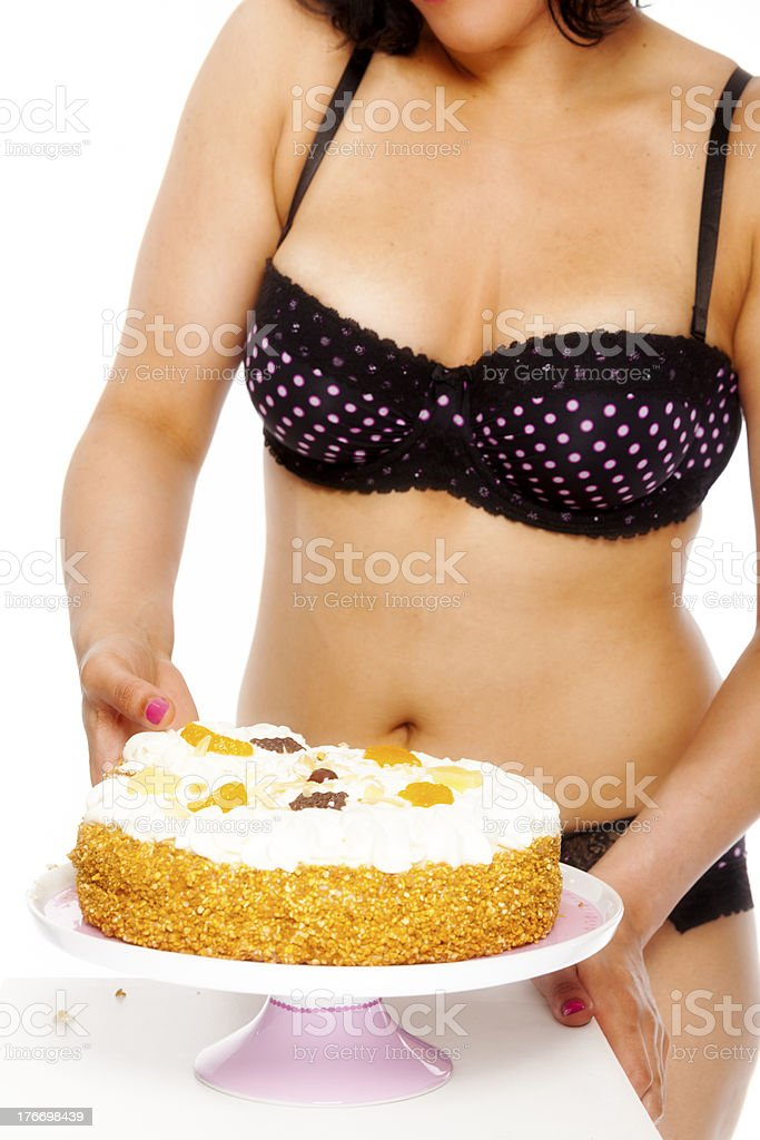 Woman in lingerie, picking up a piece of cake. royalty-free stock photo