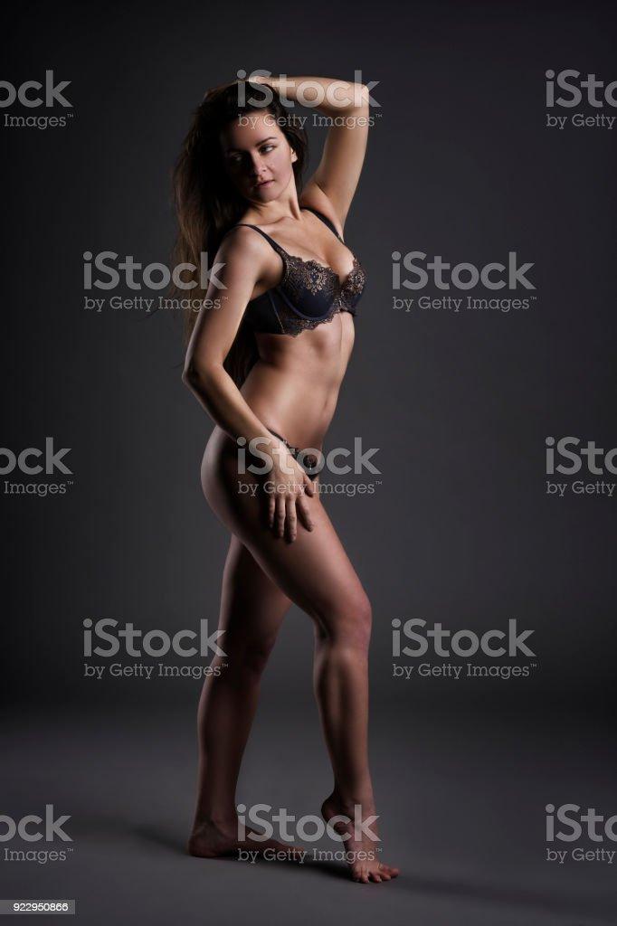 Mujer en ropa interior posando sobre fondo gris studio - foto de stock