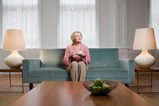 frau im wohnzimmer - seniorenwohnungen stock-fotos und bilder