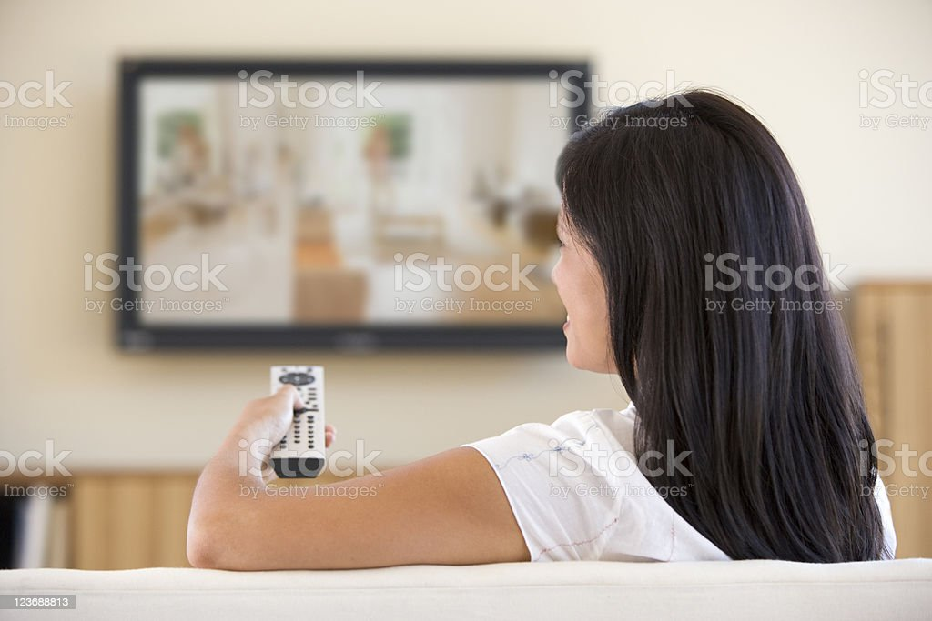 Woman in living room watching television stock photo