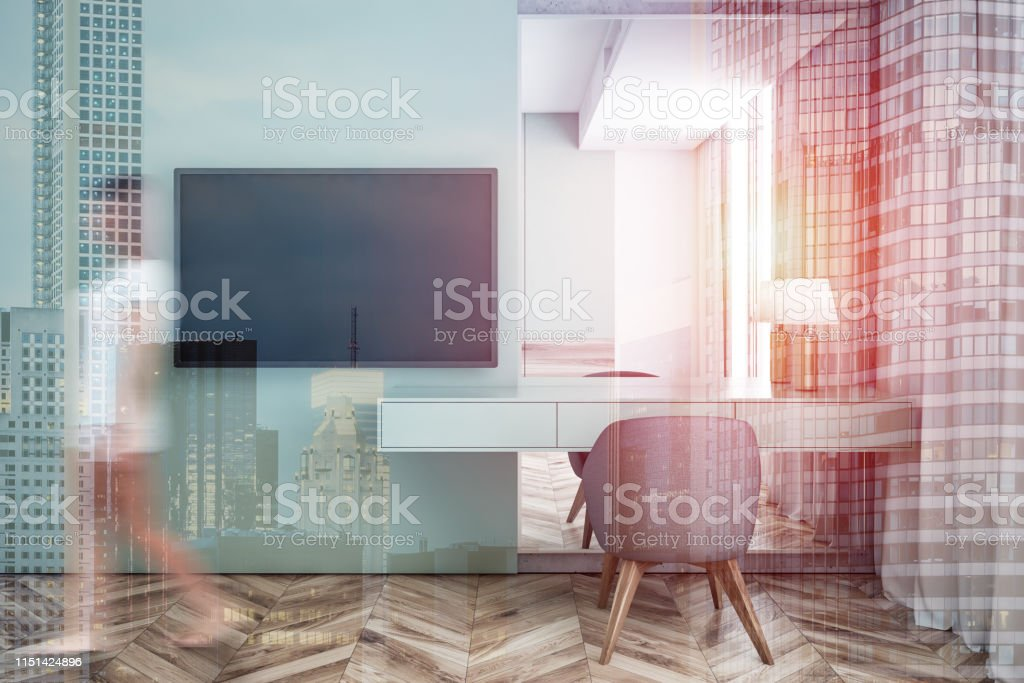 Young woman in pajamas walking in modern living room with green...