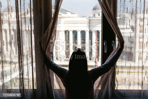 949450544 istock photo Woman in lockdown looking through the window 1220605782