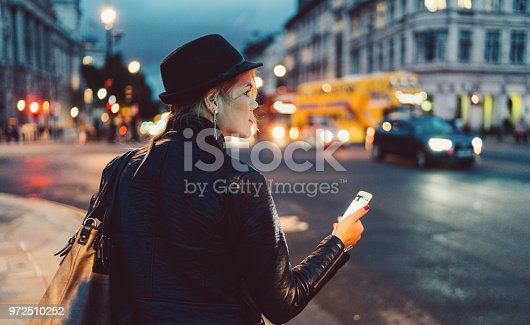 istock Woman in London at night waiting for a taxi 972510252