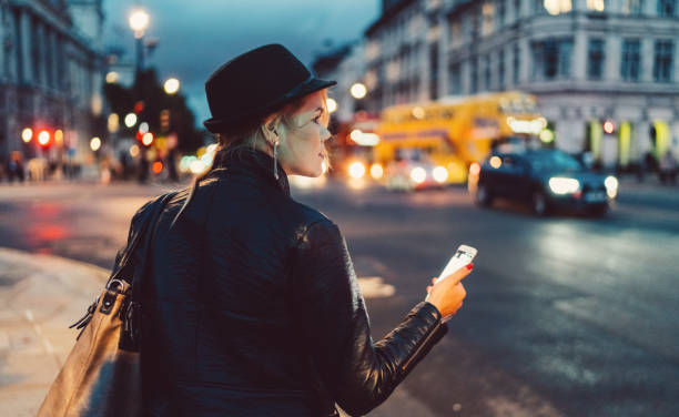 Woman in London at night waiting for a taxi stock photo