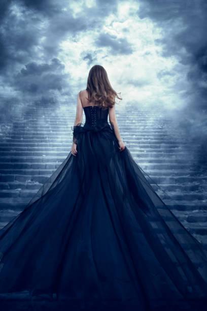 Woman in Long Dress Rear View Climbing Stairs to Sky, Girl Raising Dark Night Way stock photo
